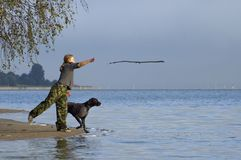 Girl play with dog. At the water royalty free stock image