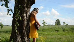Girl play guitar tree. Cute girl in yellow dress relax playing guitar near old birch tree trunk stock footage