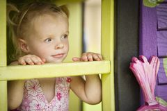Girl in a play house. A young girl plays in a playhouse at the park stock images