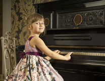 Girl play the piano and look back royalty free stock photos