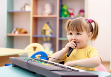 Girl play on a piano and sing in microphone. Little girl play on a piano and sing in preschool Stock Photo