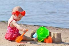 Girl play sand castle. Infant girl on a beach play with toys Stock Photos