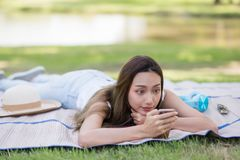 girl play smartphone in summer park Stock Photography