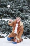 Girl play snowballs in winter forest at day. Fir trees with snow. Redhead woman full length. Royalty Free Stock Photos