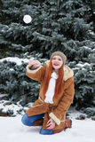 Girl play snowballs in winter forest at day. Fir trees with snow. Redhead woman full length. Stock Photography
