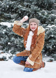 Girl play snowballs in winter park at day. Fir trees with snow. Redhead woman full length. Stock Photography