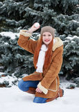 Girl play snowballs in winter park at day. Fir trees with snow. Redhead woman full length. Royalty Free Stock Image