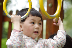 Girl  play the swinging rings. A chinese girl playing in amusement park Stock Photo