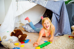 Girl in a play tent. Happy girl is playing in a tent at home royalty free stock image