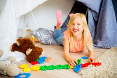 Girl in a play tent. Happy girl is playing in a tent at home stock image