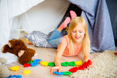 Girl in a play tent. Happy girl is playing in a tent at home royalty free stock photos
