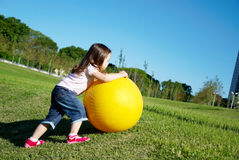 Girl play with yellow ball Stock Photos