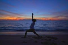 Girl play yoga on the beach Stock Photos