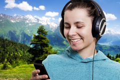 Girl with player and headphones on a clear sunny day on mountain nature landscape background listening to pop music. Stock Images