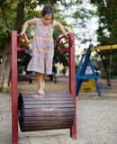 Girl in a playground. Girl on a Walking Barrel in a playground Stock Image