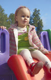 Girl on the playground. Small girl on the playground in one summer day royalty free stock photo