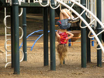 Girl on the Playground. Little girl hanging upside down on monkey bar playground equipment. No recognizable face is shown stock photos