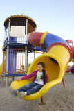 Girl is in playground. The girl slides in playground. Blurriness on girl gives dynamism stock photography