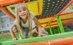 Girl on playground. A girl on a bouncy castle or padded playground, behind a net Royalty Free Stock Photo