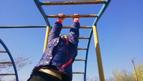 The girl on the playground climbs on the handle and horizontal bar. The girl on the playground climbs on the handle and horizontal bar stock video footage