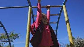 The girl on the playground climbs on the handle and horizontal bar. The girl on the playground climbs on the handle and horizontal bar stock video