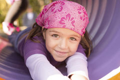 Girl at the playground. Cute little girl at a playground chute Royalty Free Stock Image