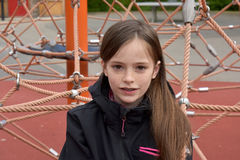 Girl at playground. Cute teenage girl climbing at playground stock image