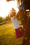Girl in a playground. Girl at the rings in a playground Stock Photography