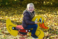 Girl at playground on a rocking duck Stock Photos