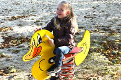 Girl at playground on a rocking duck Royalty Free Stock Image