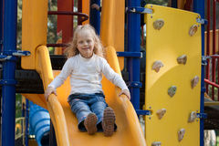 Girl On A Playground Slide. Smilling Girl On A Yellow Playground Slide Stock Image