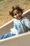 Girl on playground slide. Pretty little girl playing on a playground slide Royalty Free Stock Photo
