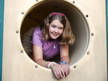 Girl in playground tunnel. Girl emerging from playground tunnel royalty free stock photos