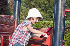 Girl at playground in wooden car Stock Images