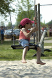 Girl playing. Little cute caucasian girl playing on a swing in the sand on the beach holding the chains fast royalty free stock photography