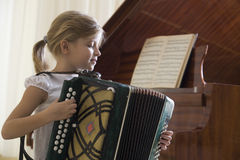 Girl Playing Accordion. Side view of a young girl playing the accordion stock images