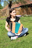 Girl playing on an accordion. Young woman - smiling girl sitting on green grass and playing on an accordion royalty free stock photo
