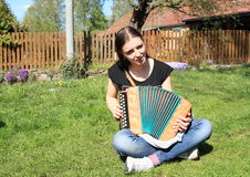 Girl playing on an accordion. Young woman - smiling girl sitting on green grass, singing and playing on an accordion stock images