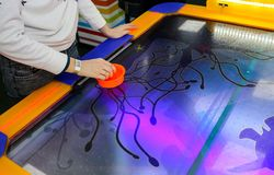 Girl is playing air hockey game and holding striker. Mallets and puck in hands. Violet table with pattern. Game in entertainment. Center. Table play. Fun and stock image