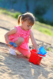 Girl playing alone in the sandpit Royalty Free Stock Image
