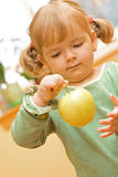 Girl playing with apple Stock Photos