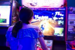 Girl playing in the arcade entertainment center. Rear view Royalty Free Stock Images