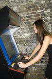 Girl Playing an Arcade Game. A young woman is playing a free standing arcade game Royalty Free Stock Photo