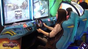 Girl playing auto simulator video arcade game. Moscow, Russia - March, 2017: Girl playing auto simulator video arcade game stock video