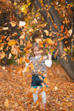 Girl is playing with autumn leaves Stock Image