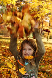 Girl  playing with autumn leaves up in the air Royalty Free Stock Photography