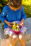 Girl playing with baby duck Royalty Free Stock Image