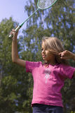 Girl playing badminton. Girl playing with racket on the lawn in summer Stock Images