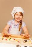 Girl playing baker, making dough using rolling pin Royalty Free Stock Photo