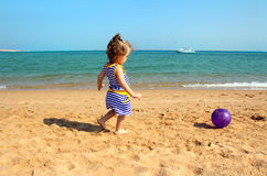 Girl playing with ball on beach Stock Image